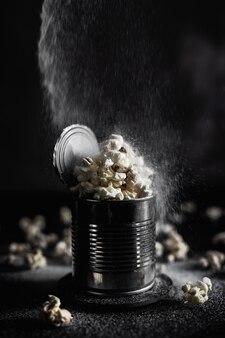 Popcorn salato in una latta d'acciaio su fondo scuro, foto lunatica