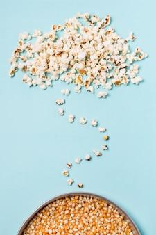 Popcorn sopra i semi del popcorn su sfondo blu