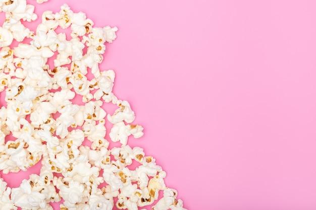 Popcorn su sfondo rosa. sfondo di film o tv, bordo, cornice. vista dall'alto copia spazio