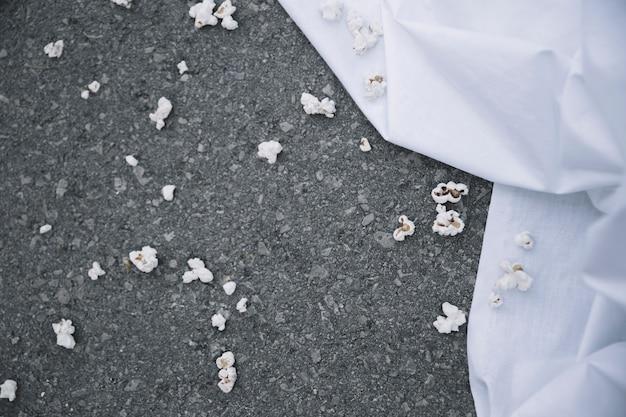 Popcorn su un terreno vicino al lenzuolo bianco