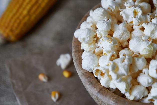 Popcorn tradizionale in una ciotola di legno e pannocchie sul tavolo.