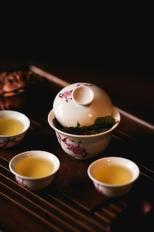 Porcellana in porcellana, tre tazze di tè cinese e rana dorata su una scrivania da tè.