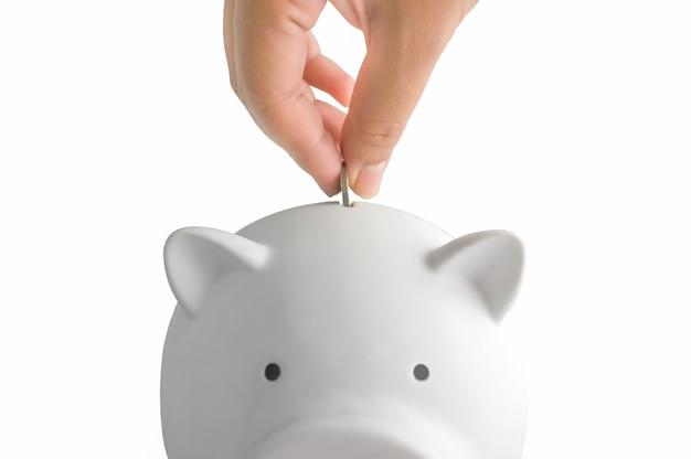 Porcellino bianco per risparmio di denaro con moneta in mano su sfondo bianco