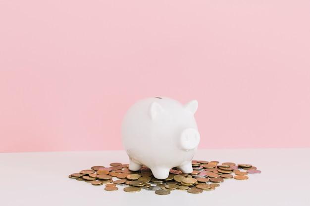 Porcellino salvadanaio bianco sopra le monete sulla tavola bianca contro fondo rosa