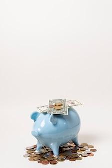 Porcellino salvadanaio blu con soldi e monete sul fondo dello spazio della copia