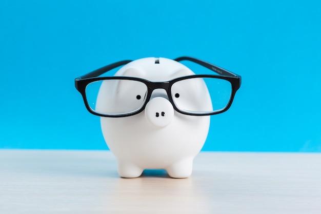 Porcellino salvadanaio con gli occhiali sul blu