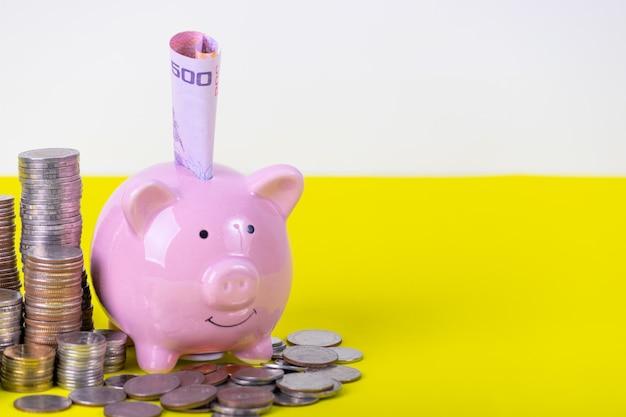 Porcellino salvadanaio con la pila di moneta sul tavolo giallo. concetto di denaro finanziario o di risparmio.