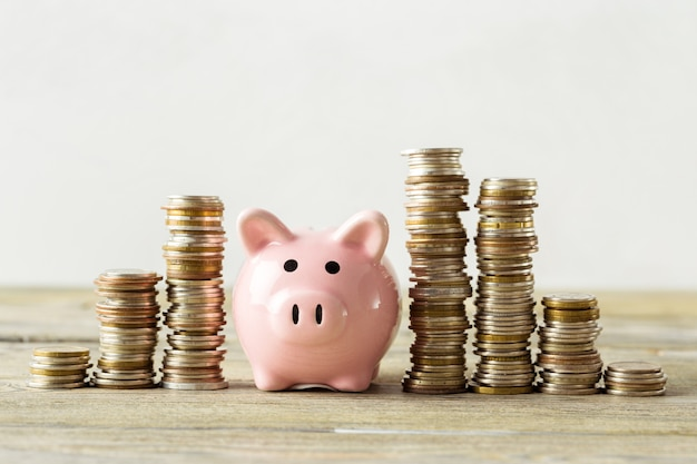 Porcellino salvadanaio con moneta sul vecchio tavolo di legno