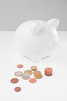 Porcellino salvadanaio dell'angolo alto con le monete accanto
