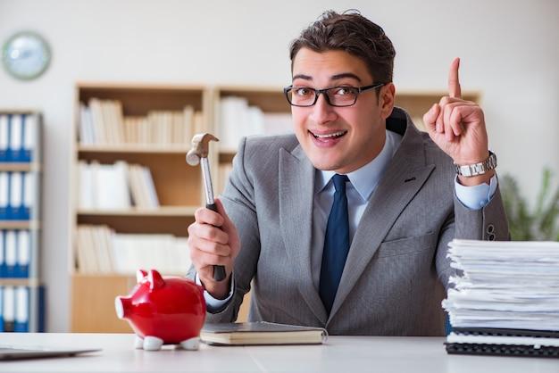 Porcellino salvadanaio di rottura dell'uomo d'affari nell'ufficio