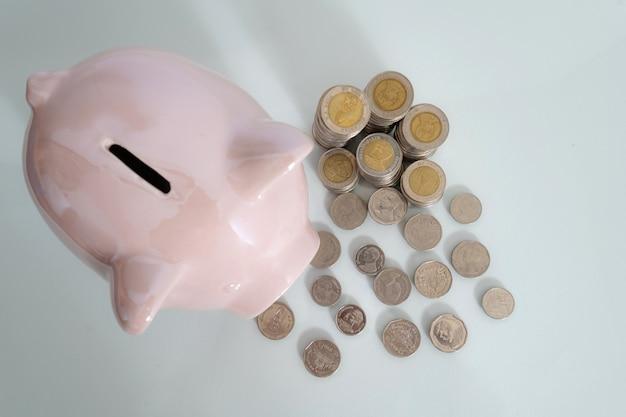 Porcellino salvadanaio e moneta su fondo nero
