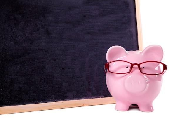 Porcellino salvadanaio rosa con gli occhiali in piedi accanto a una lavagna
