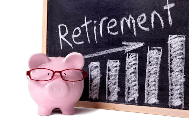 Porcellino salvadanaio rosa con i vetri che stanno accanto ad una lavagna con il messaggio di risparmio di pensione