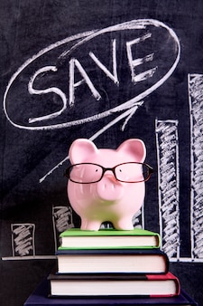 Porcellino salvadanaio rosa con i vetri che stanno sui libri accanto ad una lavagna con il grafico di crescita di risparmio.