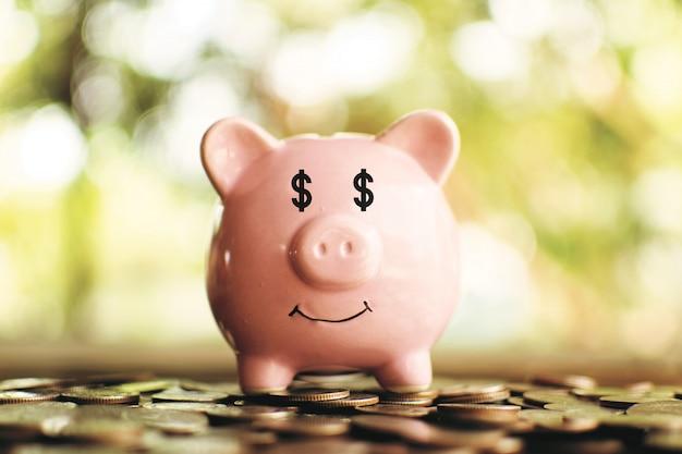 Porcellino salvadanaio rosa con monete sulla plancia di legno.