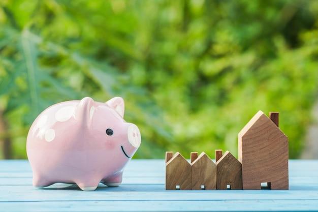 Porcellino salvadanaio rosa e casa di legno su sfondo naturale verde