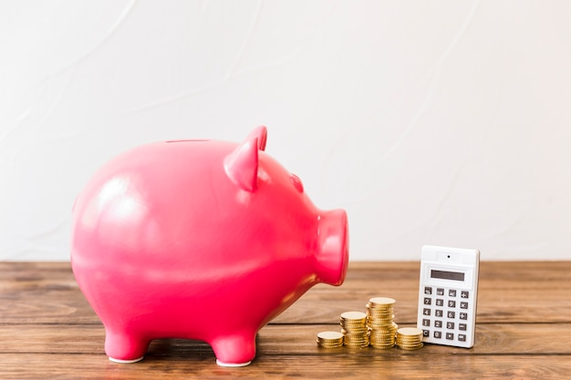 Porcellino salvadanaio rosa oltre al calcolatore e monete impilate su superficie di legno