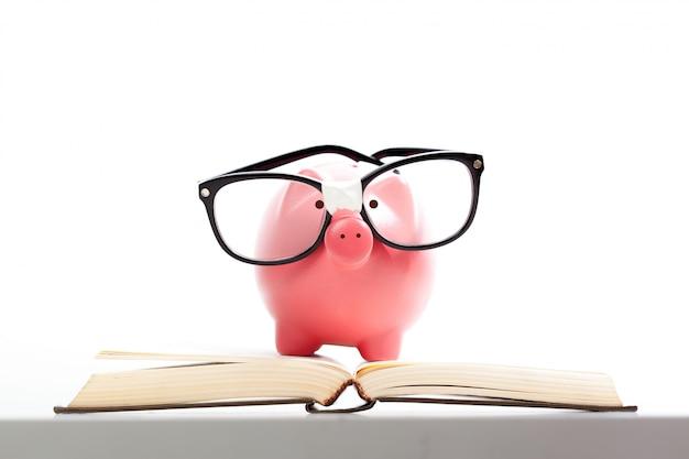 Porcellino salvadanaio su una pila di concetto del libro dei costi di istruzione