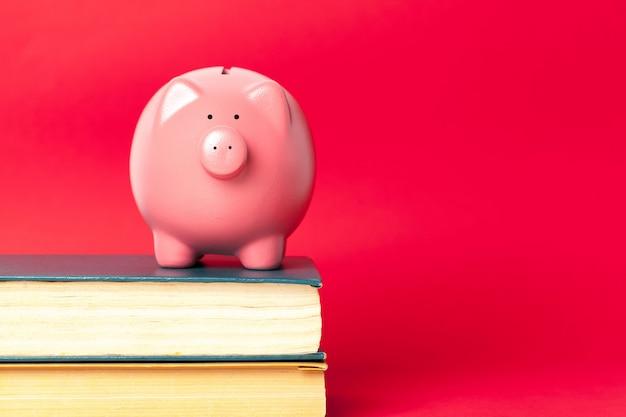 Porcellino salvadanaio su una pila di concetto del libro di costi di istruzione