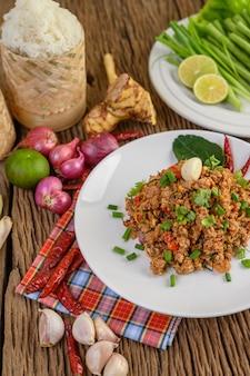 Porco tritato piccante su un piatto bianco e su una scatola di riso appiccicoso