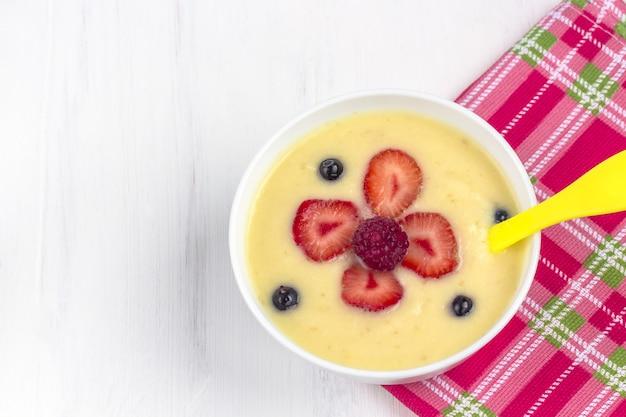 Porridge colazione sana per i bambini. ciotola di alimenti per bambini su un tessuto. il concetto di corretta alimentazione e cibo sano.