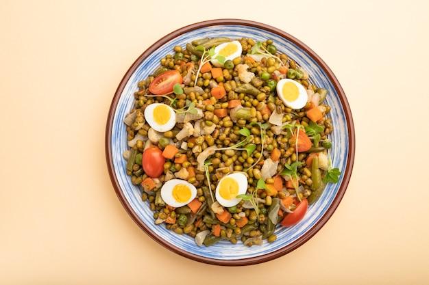Porridge di fagioli mung con uova di quaglia, pomodori e germogli microgreen su un tavolo color arancio pastello. vista dall'alto, da vicino.