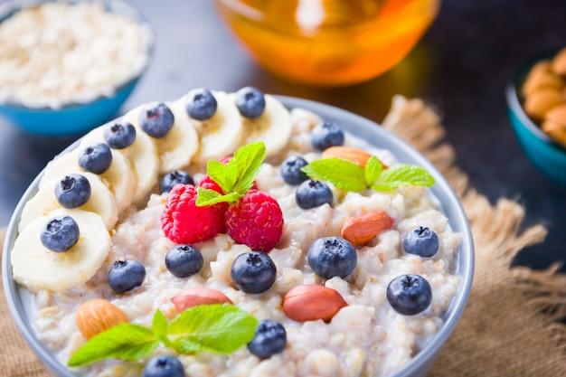 Porridge di farina d'avena con bacche, frutta e miele su sfondo scuro
