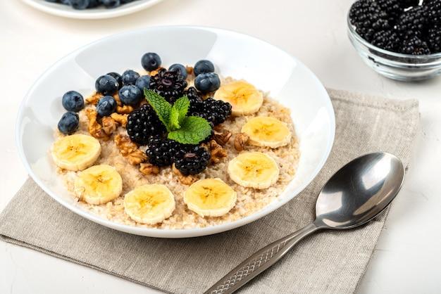 Porridge di farina d'avena con banane, noci, more, mirtilli, miele e menta in una ciotola bianca su sfondo bianco. colazione salutare e cibi dietetici fatti in casa.