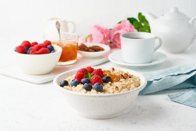 Porridge di farina d'avena con mirtilli, lamponi, marmellata e noci, vista dall'alto. colazione con frutti di bosco