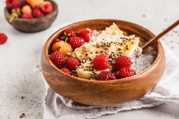 Porridge di farina d'avena con semi di chia, bacche, burro di arachidi e semi di canapa in ciotola di legno, sfondo bianco.