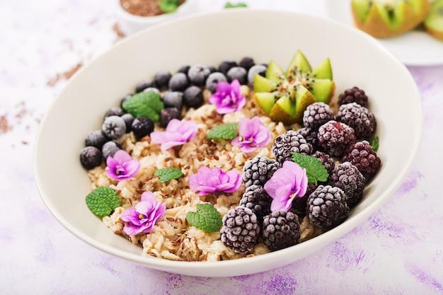 Porridge di farina d'avena gustoso e sano con frutta, bacche e semi di lino. colazione salutare. cibo fitness. nutrizione appropriata.