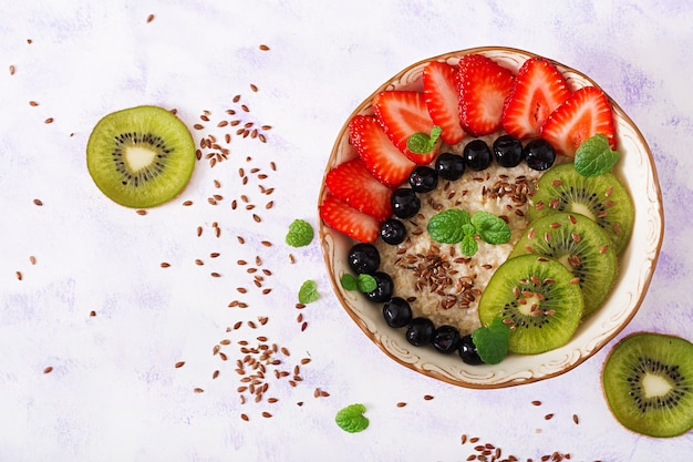 Porridge di farina d'avena gustoso e sano con frutta, bacche e semi di lino.