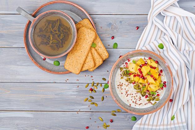 Porridge di farina d'avena gustoso e sano con mango, melograno e semi. colazione salutare. cibo fitness. nutrizione appropriata. vista dall'alto