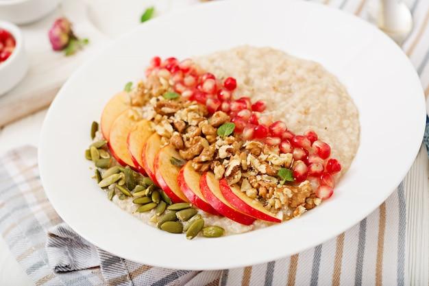 Porridge di farina d'avena gustoso e sano con mele, melograno e noci. colazione salutare. cibo fitness. nutrizione appropriata
