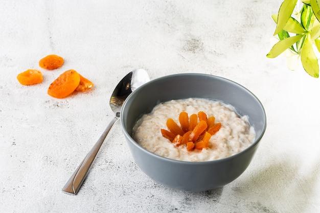 Porridge di farina d'avena o avena di porridge o cereali per la colazione con albicocche secche isolate su fondo di marmo bianco. cibo fatto in casa. gustosa colazione messa a fuoco selettiva. foto orizzontale.