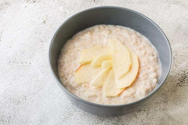 Porridge di farina d'avena o avena di porridge o cereali per la colazione con la mela isolata su fondo di marmo bianco. cibo fatto in casa. gustosa colazione messa a fuoco selettiva. foto di hotizontal.