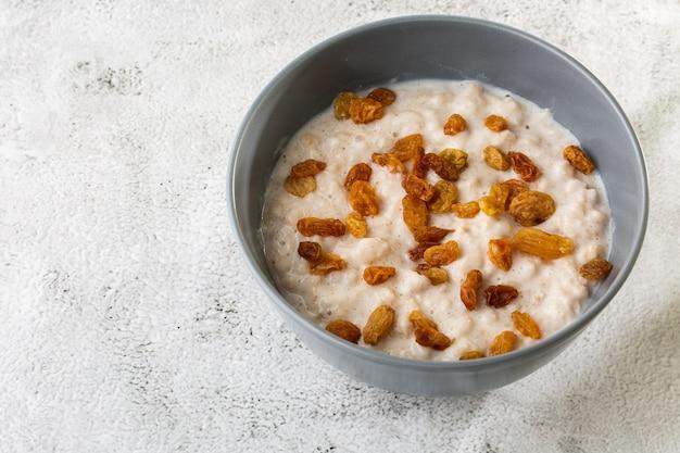 Porridge di farina d'avena o avena di porridge o cereali per la colazione con uvetta isolato su sfondo di marmo bianco. cibo fatto in casa. gustosa colazione messa a fuoco selettiva. foto orizzontale.