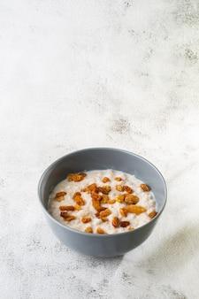 Porridge di farina d'avena o avena di porridge o cereali per la colazione con uvetta isolato su sfondo di marmo bianco. cibo fatto in casa. gustosa colazione messa a fuoco selettiva. foto verticale.