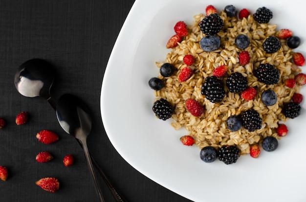 Porridge di farina d'avena sano con mix di frutti di bosco sul buio