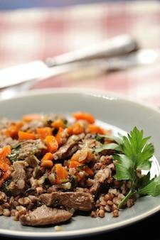 Porridge di grano saraceno con carne in umido e carote