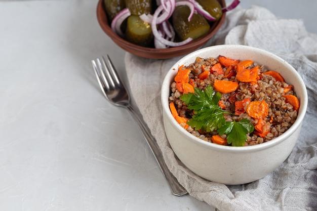 Porridge di grano saraceno in una ciotola con carote in umido. decorato con foglie verdi.