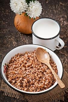 Porridge di grano saraceno in una vecchia ciotola di ceramica su uno stile rustico