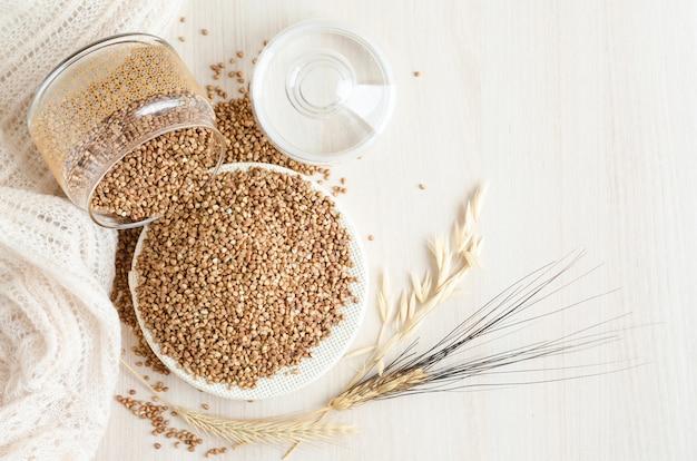 Porridge di grano saraceno spruzzato dal barattolo di vetro su fondo di legno bianco, spazio della copia. cereali, cereali, colture, grano, avena. cibo sano e nutriente. disavanzo