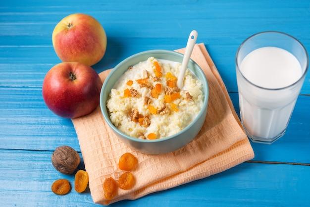 Porridge di latte di miglio con mela, noci e albicocche secche su uno sfondo blu di legno