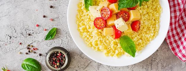 Porridge di miglio con formaggio, burro e basilico in ciotola bianca. cibo gustoso. prima colazione. vista dall'alto. disteso