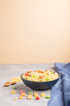 Porridge di miglio con frutta candita e mandorle in ciotola di ceramica blu su una parete grigia e arancione. vista laterale, messa a fuoco selettiva, copia spazio.