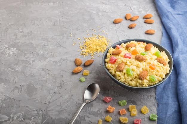 Porridge di miglio con frutta candita e mandorle in ciotola di ceramica blu su una superficie di cemento grigia. vista laterale, copia spazio.