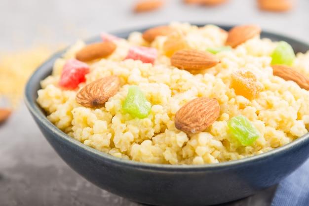 Porridge di miglio con frutta candita e mandorle in ciotola di ceramica blu su una superficie di cemento grigia. vista laterale, messa a fuoco selettiva.