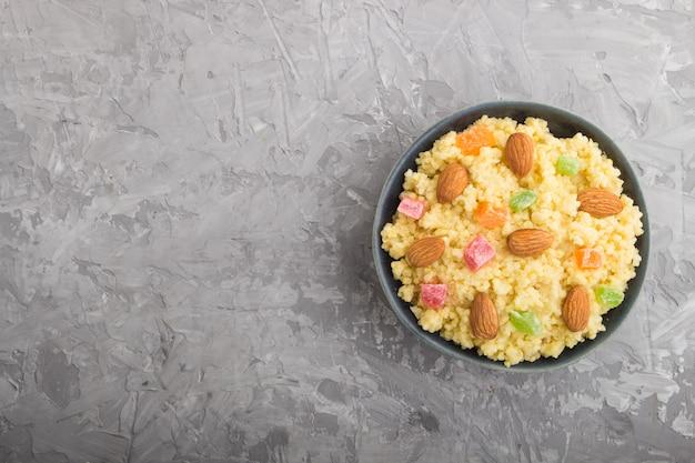 Porridge di miglio con frutta candita e mandorle in ciotola di ceramica blu su uno sfondo di cemento grigio. vista dall'alto, copia spazio.
