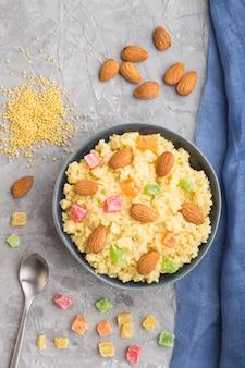 Porridge di miglio con frutta candita e mandorle in ciotola di ceramica blu su uno sfondo di cemento grigio. vista dall'alto, da vicino.